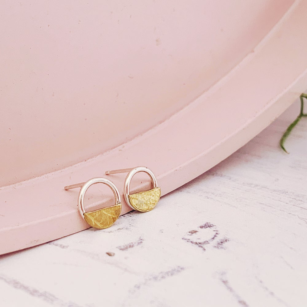 Image of Minimal silver circle studs with a brass semi circle