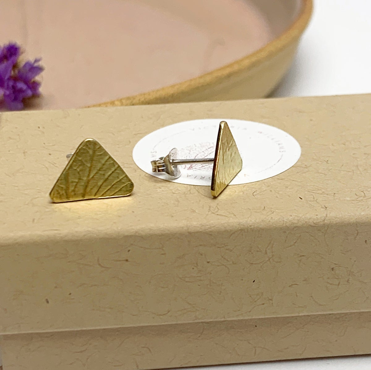 Image of Brass triangle studs with petal imprint.
