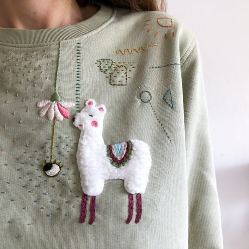 Image of The Last Alpaca on a sage green pullover - hand embroidered, organic cotton, GOTS certified
