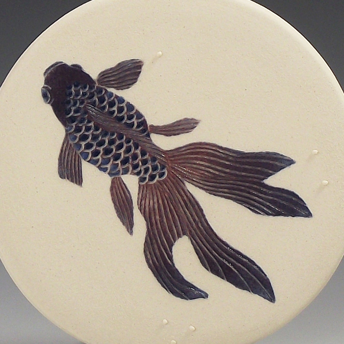 One fancy fish in purple ceramic wall hanging