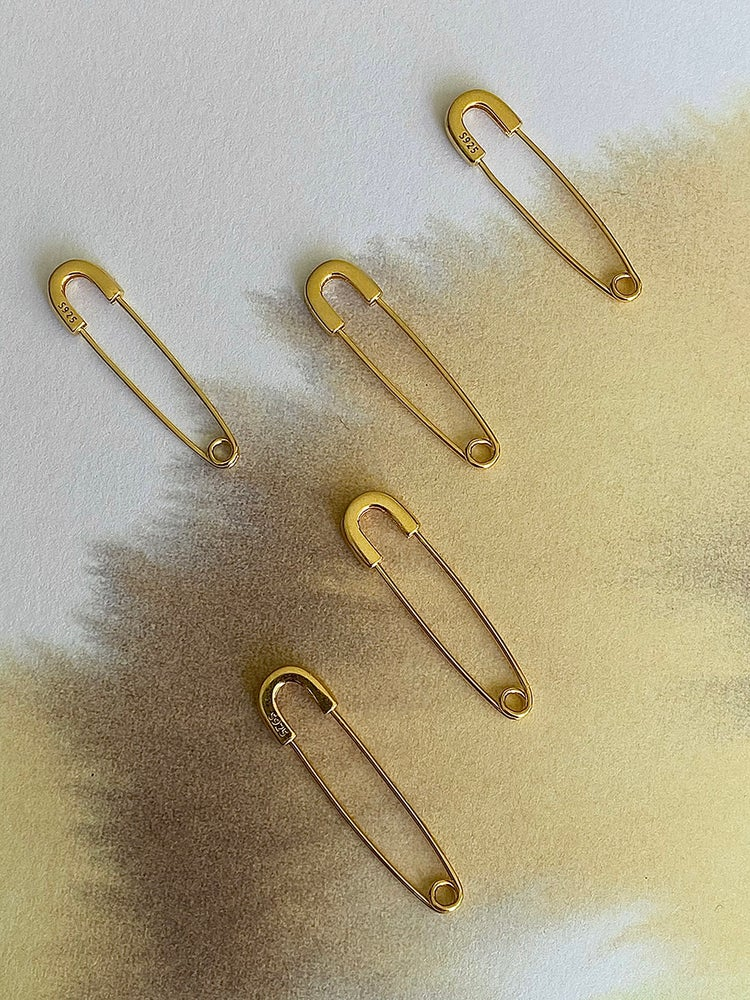 """FUN AND QUIRKY  This light pieces hook very comfortably through the ears, fastening works the same as a normal safety pin, you pierce it trough your ear, upside down or the other way around. The single safety pin earring is gold plated 925 sterling silver and 3cm / 1,18"""" long"""