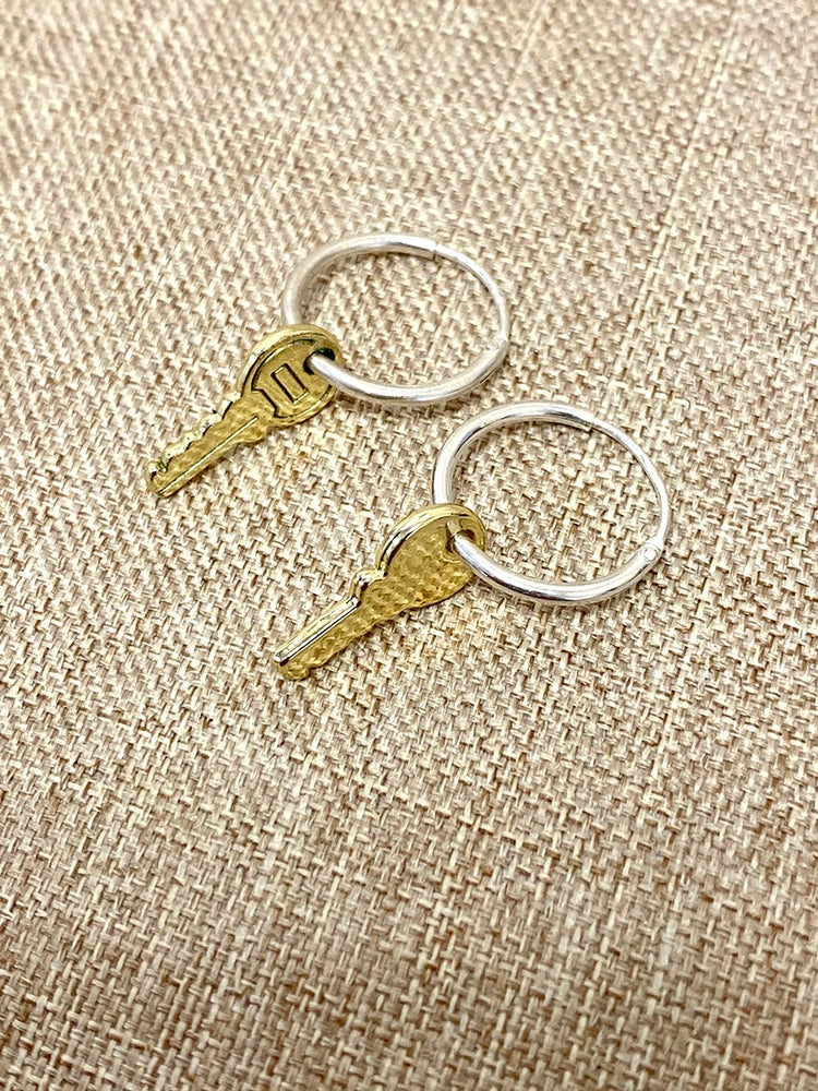 """KEYS SYMBOLISE FREEDOM, THEY OPEN UP AND LOCK PRECIOUS THINGS AWAY. KEYS LET US INTO UNKNOWN WORLDS.  It is a pathway, freedom, an expression of desire to open up the world. The opening of many exciting doors to come.  The unlock earring features a small key charm pendant 18 mm - 0,7"""", which is carried by a delicate tiny hoop, available in 13 and 15mm - 0,5 and 0,6"""" diameter. (model is wearing 13mm hoop) Inform us when placing an order.  Notably, the key is detailed ..."""
