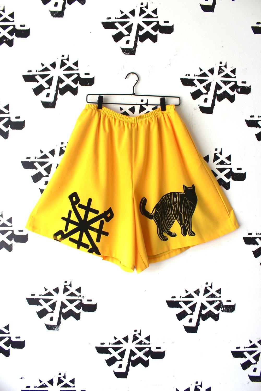 shiny black shorts in yellow