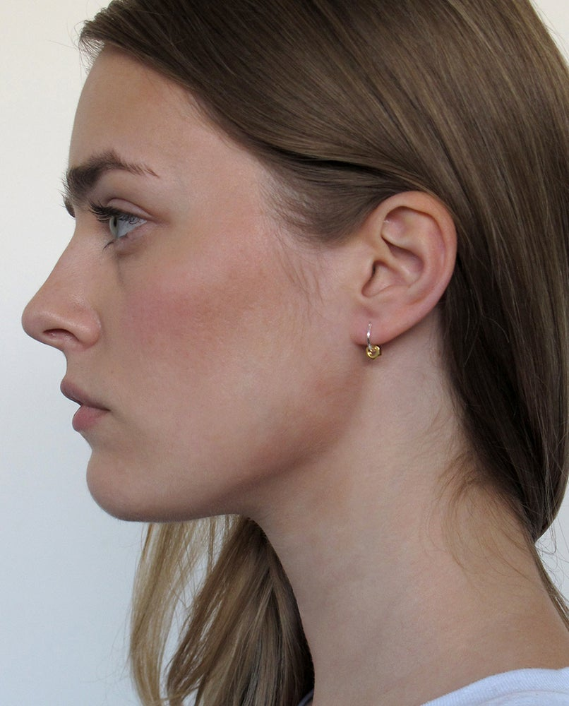 THE LIGHT IS BEAUTIFULLY REFLECTED THE BY THE SURFACES OF THE NUT   High quality 925 silver thin and delicate hoop earring adorned with gold plated nut  Hoops are available in 11, 13 and 15mm diameter, inform us when placing an order. Fist model on the picture wears a 13mm and the second a 11mm.  Put on and never take off!  To wear as a single in a 2nd or 3rd piercing, but we also love the cleanness of them as a matching pair.  Possible to buy a single piece to mix and match