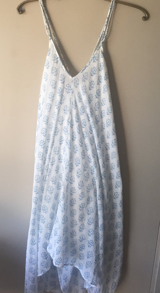 Image of Love stitch blue floral design high low cotton dress. Crosses in back
