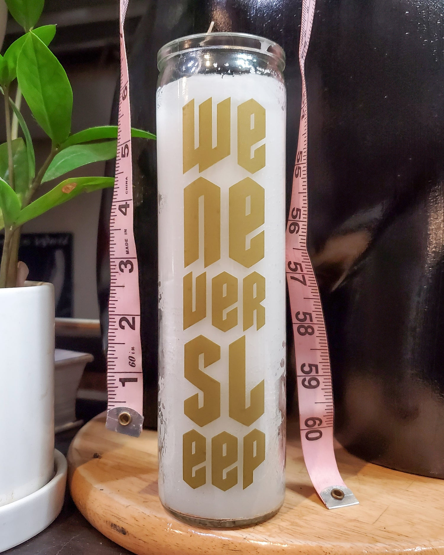 """""""We Never Sleep"""" Candle, gold on white"""