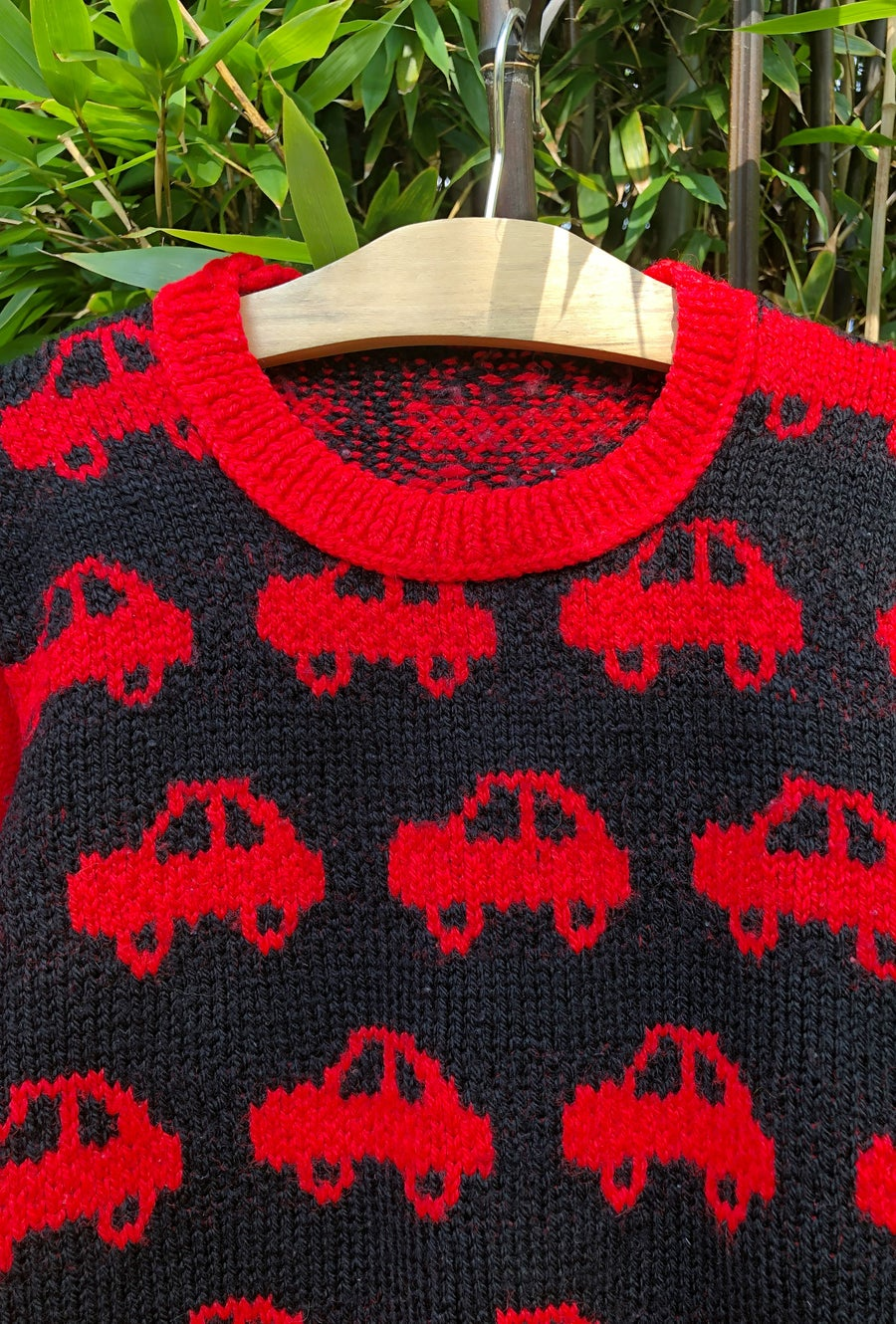 Image of Black and red hand-knitted jumper with cars. Age 4-5yrs.