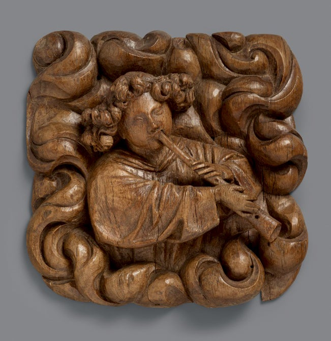 Image of A superbly carved 15th century wood relief of an angel blowing a shawm