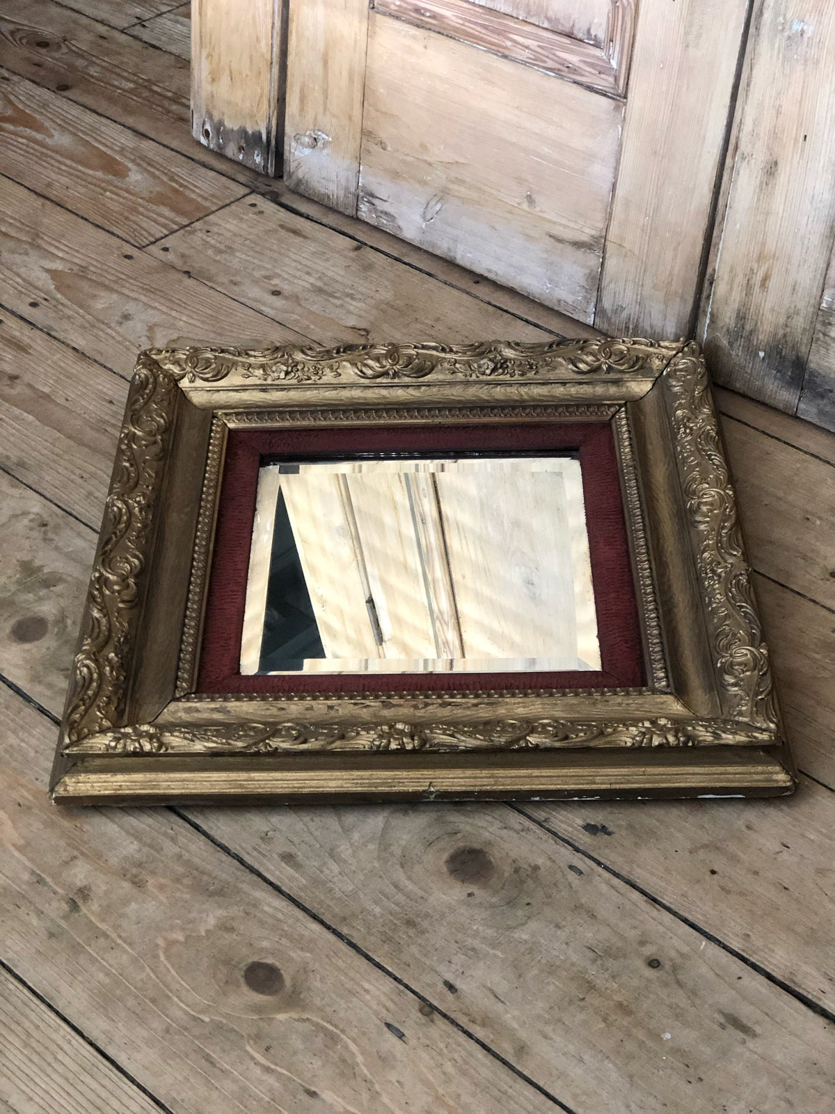 Image of Ornate gold mirror with red trim