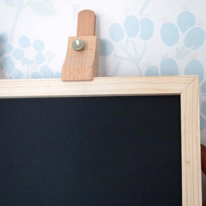 rectangular wooden chalkboard with brown border and stand