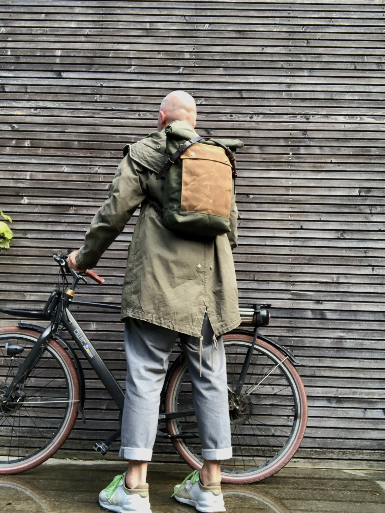 Image of olive green backpack medium size rucksack in waxed canvas, with volume front pocket and double layer