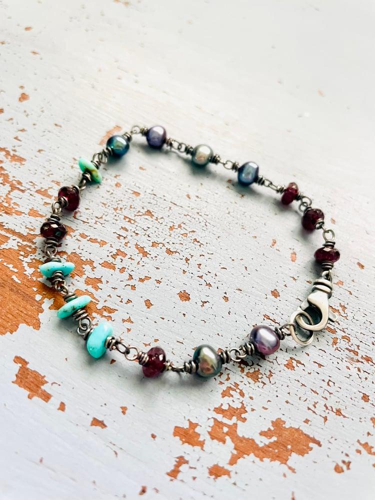 Image of peacock pearl and garnet bracelet